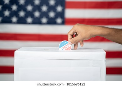 Concept of USA elections, Close up of Hands Putting I Voted sticker inside Ballot box with US flag as background.