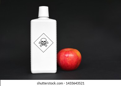 Concept for usage of dangerous pesticides in agricultural food products with red apple next to white bottle with poisonous warning label with skull on black background