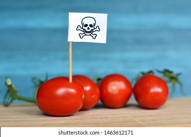 Concept for usage of dangerous pesticides in agricultural food products with red tomatoes and toxic warning sign