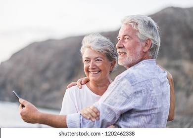 concept of vacation, technology, tourism, travel and people - happy senior couple with cell phone phone on pebble beach laughing and joking hugging and making photo. White hair