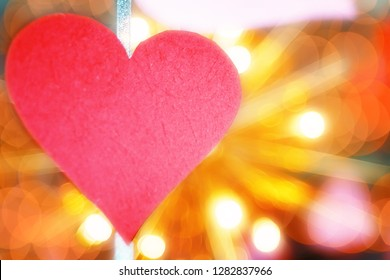 Concept of Valentines day. cut out red paper in the form of a heart on the background of bright bulbs