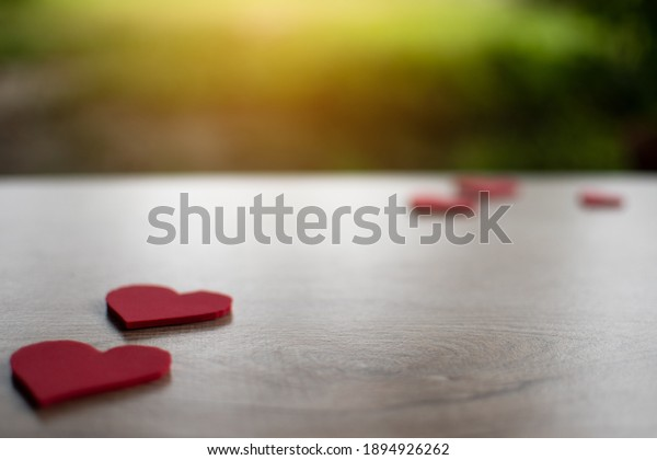 Concept valentine's day, a red heart symbol placed on a wooden table. Take a close-up and selective focus, copy space for design and text. Blurred background.