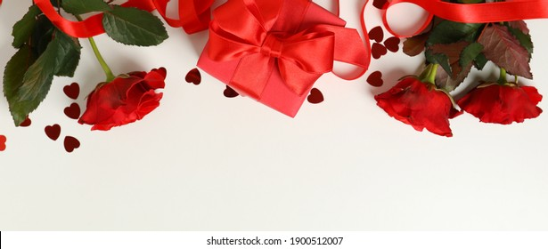 Concept of Valentine's day with roses and gift box on white background