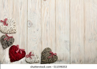 Concept Of Valentine's Day. Wicker hearts on wooden background white.