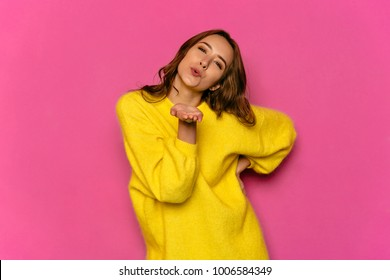 Concept of Valentine's day. Young pretty woman, dressed in yellow soft sweater, giving air kiss, looking at camera. Isolated on pink background.