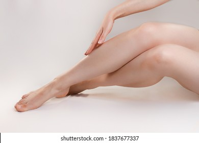 The concept of varicose disease and cosmetology. The woman crosses her legs gracefully and runs her hand over them. Copy space