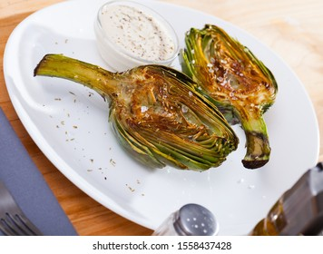 Concept of vegetarian food. Chopped fried artichokes sprinkled with koshering salt served with white sauce