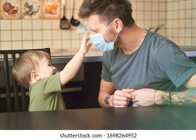 Concept virus protection measure. Father teaches son put mask on face, explains danger flu, horror coronavirus. Man and child sitting kitchen dressed in casual clothing t-shirts, quarantined at home