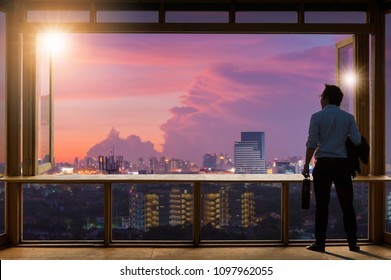 Concept vision, Young businessman wearing comfortable casual suit jacket standing holding a work bag in Working room near the glass window and looking through the modern buildings in the skyline.