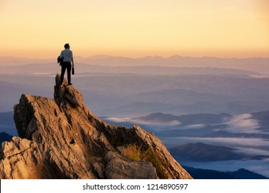 Concept vision, Young businessman wearing comfortable casual suit jacket standing holding business bag on top of peak mountain and looking forwards, success, competition and leader concept.