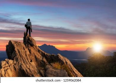 Visión conceptual, Joven empresario vestido con una cómoda chaqueta de traje casual de pie sosteniendo una bolsa de negocios en la cima de la montaña y mirando hacia el futuro, el éxito, la competencia y el concepto de líder.