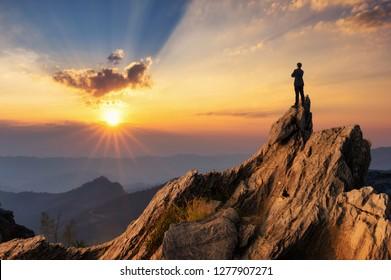 Visión conceptual, Joven empresario con una cómoda chaqueta de traje casual, abrazándose el pecho en la cima de la montaña y mirando hacia adelante, el éxito, la competencia y el concepto de líder.