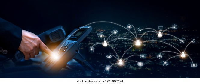 Concept of voip telecommunication, business woman pick up the handset and press the number button of ip telephone and connection line, services icon on night cityscape background