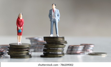 The concept of wage difference between men and women. The man and woman standing on top of the pile of coins.