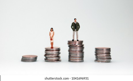 Four pile of coins and miniature people. The concept of wage disparity between men and women.