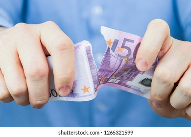 Concept of waiver of euro. A man in a blue shirt holds one euro and tears them up.