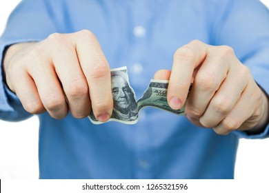 Concept of waiver of us dollars. A man in a blue shirt holds one hundred US dollars and tears them up.