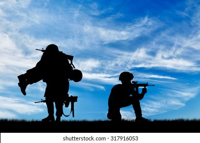 Concept of war. Silhouette of a soldier carries a wounded soldier on a background of sky