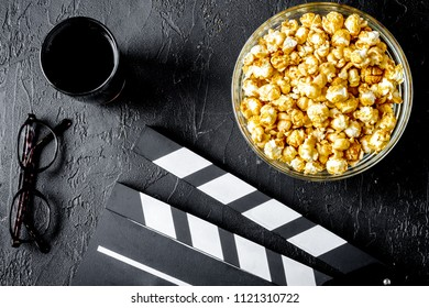 concept of watching movies with popcorn top view dark background
