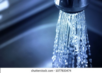 Concept water saving at home, reducing use. Water supply problems. Water tap with flowing water with spray. Selective focus