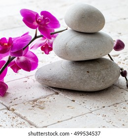 concept of wellbeing, meditation and femininity with stack of balancing pebbles or stones over beautiful orchids and limestone background