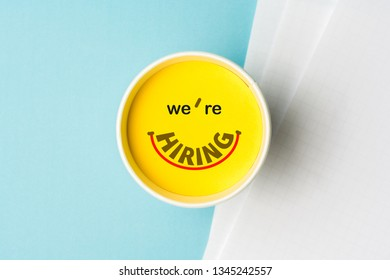 Concept of we're hiring or join our team or onboarding process. Paper cup with yellow top on desk with blank documents over blue background. Concept of summer jobs for millenials young people.