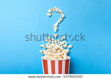 Concept of which film to choose. Spilled popcorn in the form of question mark and a paper bucket in red strip on blue background.