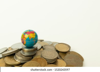 Concept of whole world stand on Money, Stack of Indian currency coins with globe above the coins on isolated background.