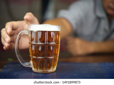 Concept of Withdrawal Symptoms from alcohol or Alcoholic diseases.Hand with a glass of beer on wood.