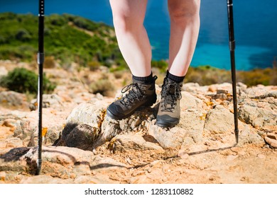 Concept of woman feet in hiking boots on the trail on the rocks above the blue ocean. The active way to spend the summer holidays.