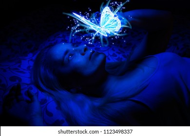 Concept of a woman laying in bed in the dark, illuminated with blue light from floating magical butterfly above her, her hand lightly touching it