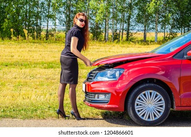 The concept of women's autonomy, self-solving problems. A woman on the side of a country road raises the hood of her car. Car breakdown on the road