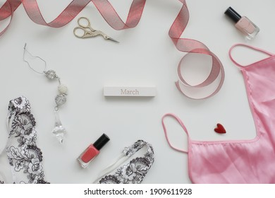 Concept Women's Day, March 8. Female underwear with a red ribbon and cosmetics on white background. Styled flat lay, top view, copy space.