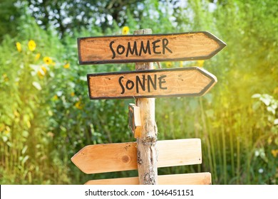 Concept: Wooden direction sign with the German words summer and sun (Sommer, Sonne)