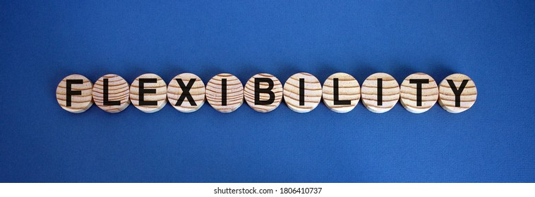 Concept word 'flexibility' on wooden circles on a beautiful blue  background. Business concept.