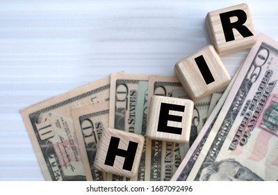 Concept of the word HEIR on cubes on dollar papers