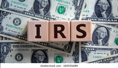 Concept word 'IRS - Internal Revenue Service' on wooden blocks on a beautiful background from dollar bills. Business concept.
