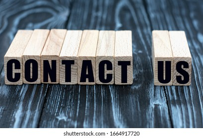 concept of words to contact us on cubes on a beautiful wooden background