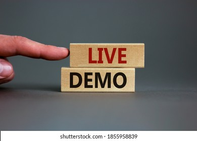 Concept words 'live demo' on wooden blocks on a beautiful grey background. Male hand. Copy space. Business concept.