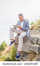 Concept: Working anytime and anywhere. Young handsome successful man is sitting on the stone and using digital tablet during summer journey in the mountains.