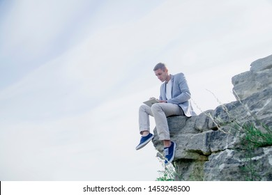 Concept: Working anytime and anywhere. Young handsome successful man is sitting on on the top of the mountain and working with digital tablet during summer journey.