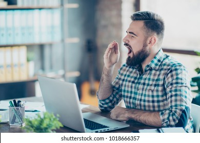 Concept of working day and night without having a recreation. Half-turned photo of exhausted powerless yawning tired young wearing casual checkered shirt office worker sitting in front of netbook