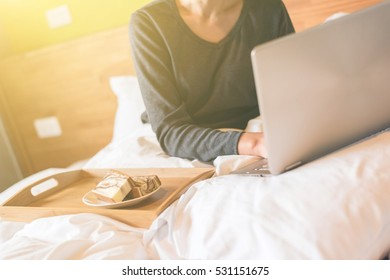 concept of working at home with woman using laptop on bed