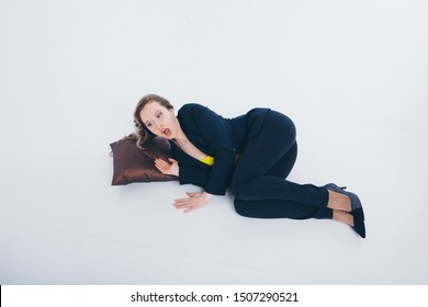 the concept of working in the office, break, sleep-hour, rush hour-the businesswoman woke up with fright. Beautiful woman on white background lying on the floor, anxiously opened her mouth, screaming