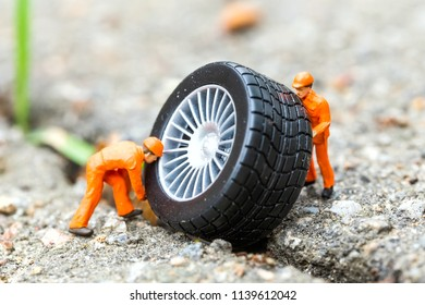 The concept of the workshop tire fitting. Miniature mechanics repairing toy car wheel, close up.