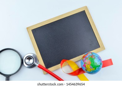 The concept of 'World Hepatitis Day' with yellow and red ribbon, world globe, stethoscope, syringe, magnifying glass and black board for your text.