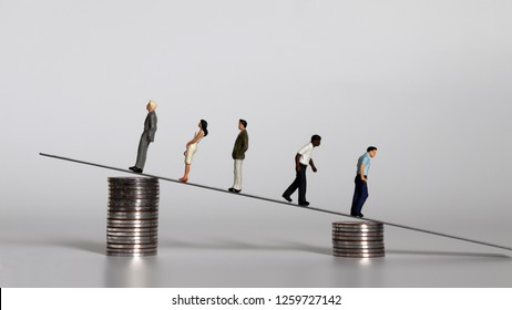 The concept of worsening income and poverty gap. Miniature people with a pile of coins.