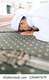 """Concept of Young Asian Malay Muslim performing prostration or """"sujud"""" during praying"""
