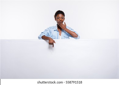 concept with young beautiful black woman leaning on an white empty and board dressed in jeans shirt and smiling presenting and pointing the subject or the text
