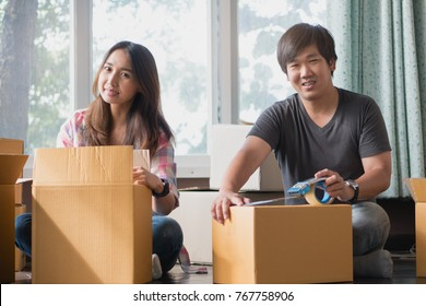 Concept young couple moving house. Asian young couple unpack cardboard box after moving in new house.